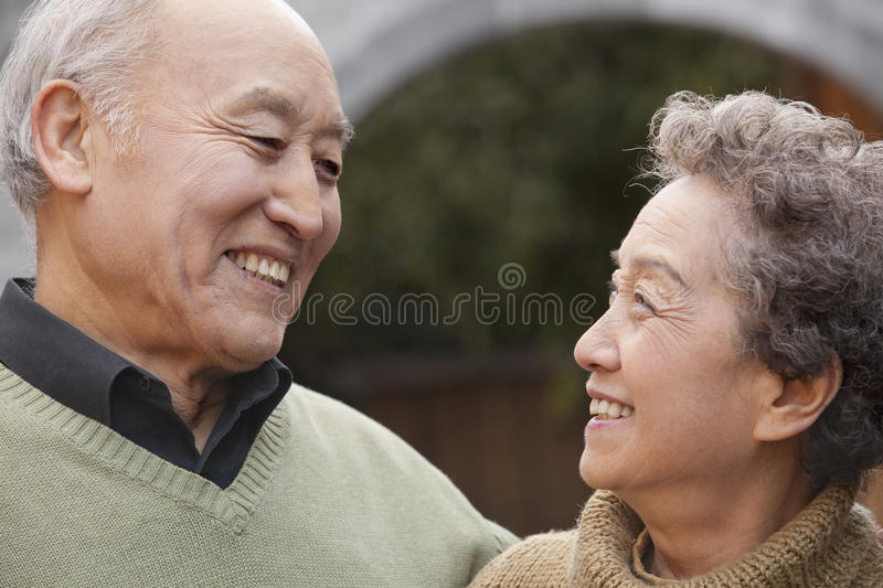 Portrait of laughing senior couple in front of round arch, Beijing stock image