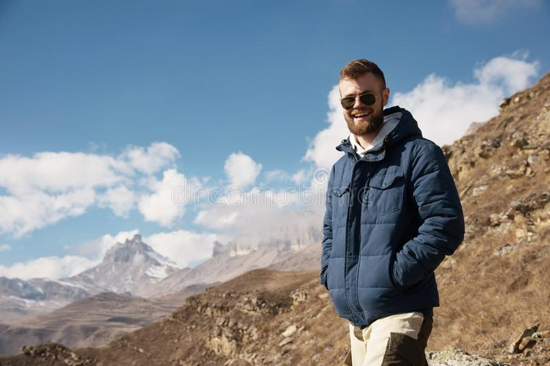 Portrait of a laughing stylish bearded man in a down jacket and sunglasses on a background of epic mountains of sky and stock images