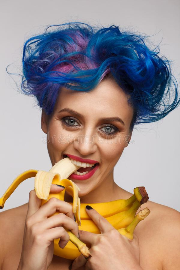 Portrait of a laughing woman with blue and pink hair eating a banana. Light gray background stock images