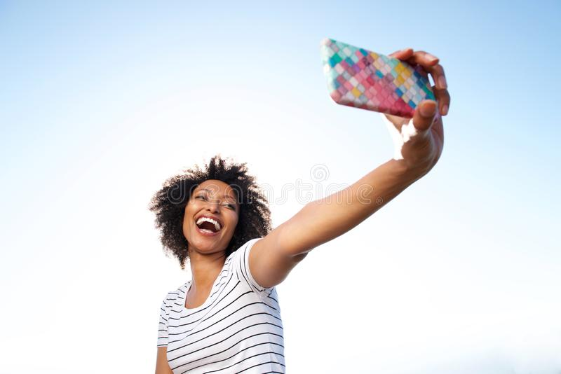 Laughing young african american woman taking selfie with smart phone outdoors. Portrait of laughing young african american woman taking selfie with smart phone stock images