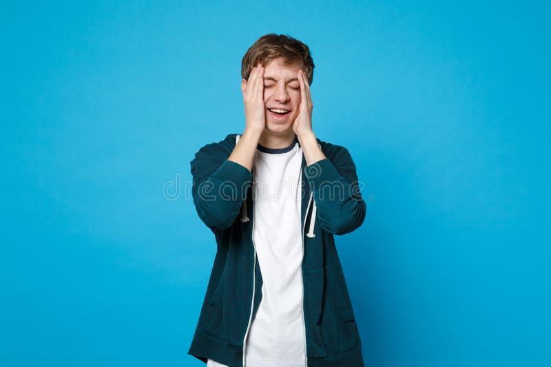 Portrait of laughing young man in casual clothes keeping eyes closed, putting hands on face isolated on blue wall stock images