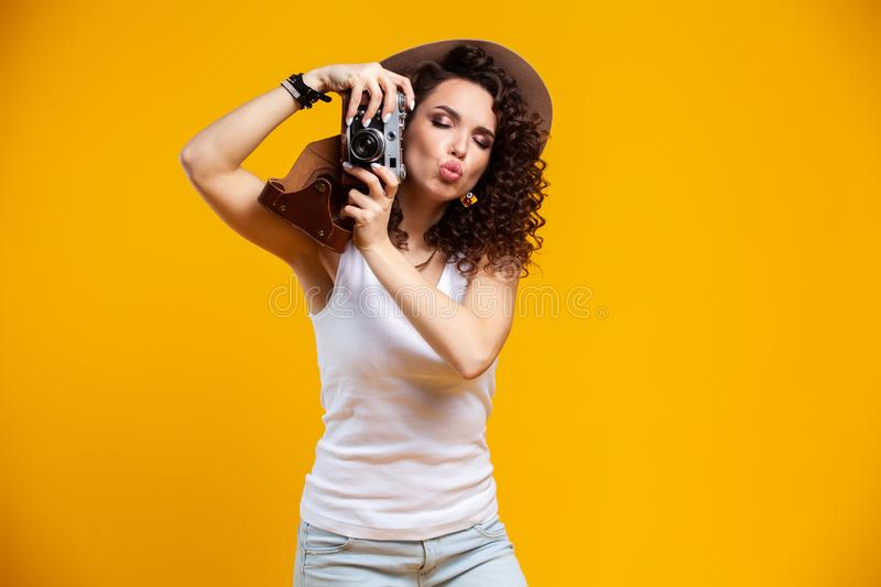 Portrait of laughing young woman taking pictures on retro vintage photo camera isolated on bright yellow background stock image