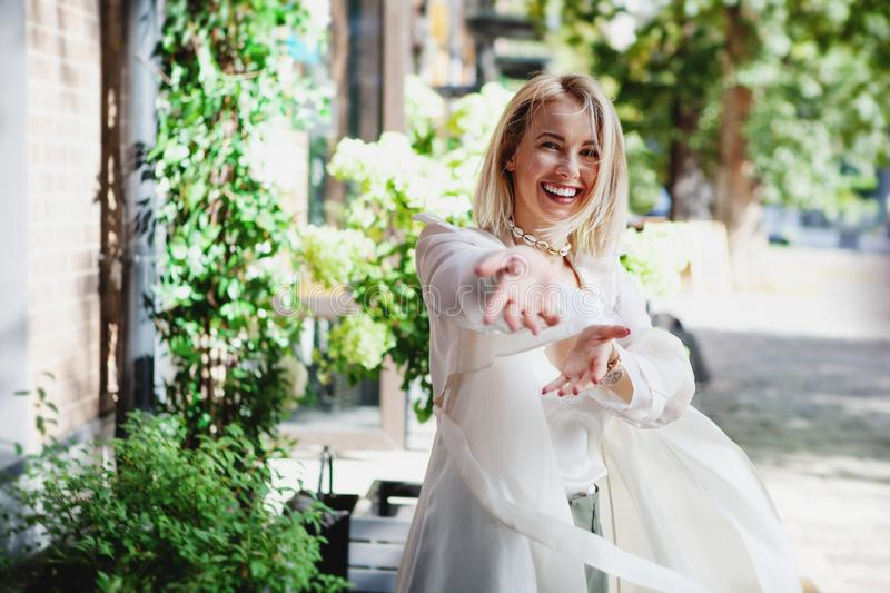 Portrait of Laughing young woman in white trench coat having fun on street. Dancing happy blonde girl pull hands forward. stock images
