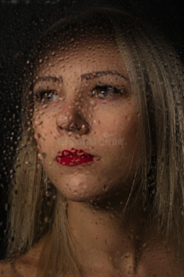 Portrait lisse de belle fille, posant derrière couvert de verre transparent par des baisses de l'eau image libre de droits