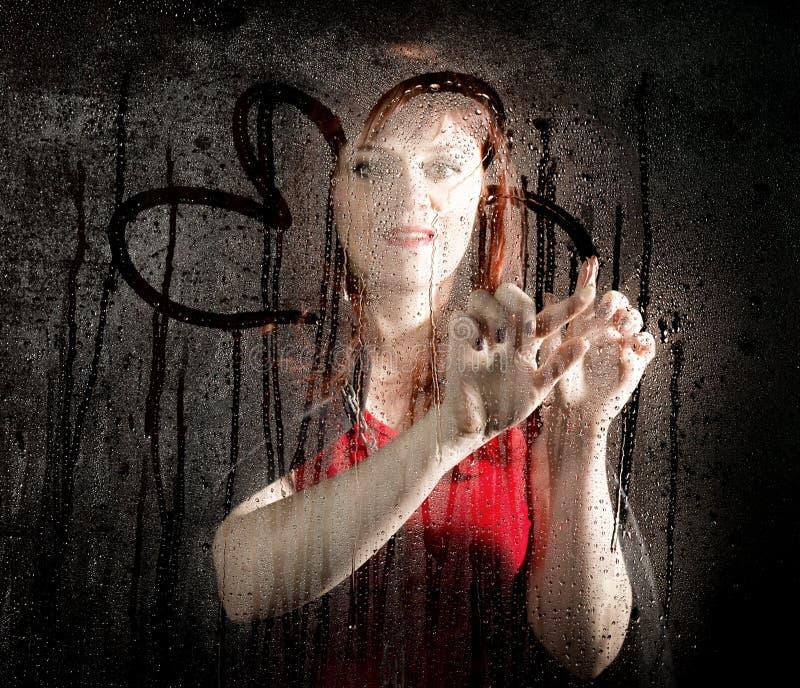 Portrait lisse de modèle femelle, posant derrière le verre transparent et peignant sur des baisses de l'eau Jeune femme de sourir image stock
