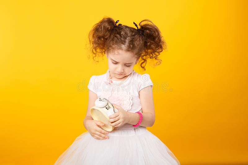 Portrait of a little adorable curly girl, looking frowned on a alarm clock, over yellow background. copy space. royalty free stock images