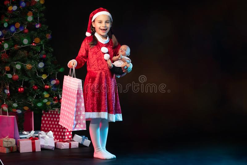 Portrait of Little Adorable Girl in Christmas Costume Holding Present Bag royalty free stock photography