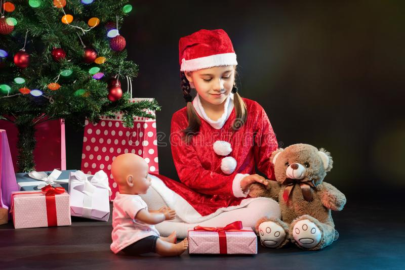 Portrait of Little Adorable Girl in Christmas Costume Holding Pr royalty free stock photography