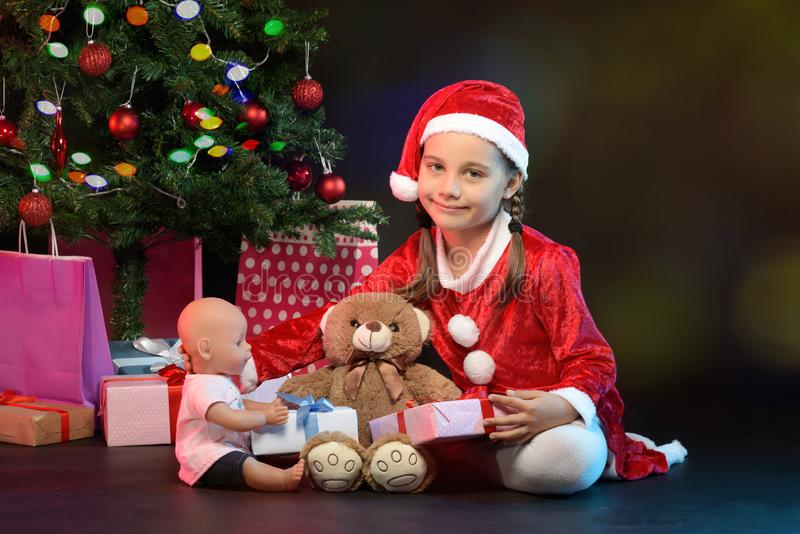 Portrait of Little Adorable Girl in Christmas Costume Holding Pr royalty free stock photos