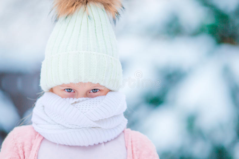 Portrait of little adorable girl in snow sunny winter day, Closeup beautiful green eyes. Portrait of little adorable girl in snow sunny winter day royalty free stock photography