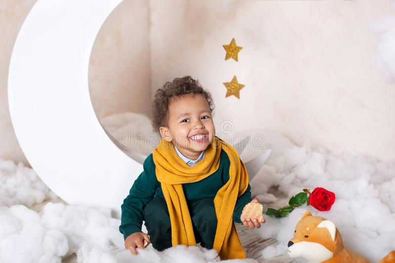 Portrait of a little African American. Baby smiles. Black boy in a green sweater and a yellow scarf smiling. Little Prince. The c. Hild eats cookies. Scandinavia stock photo