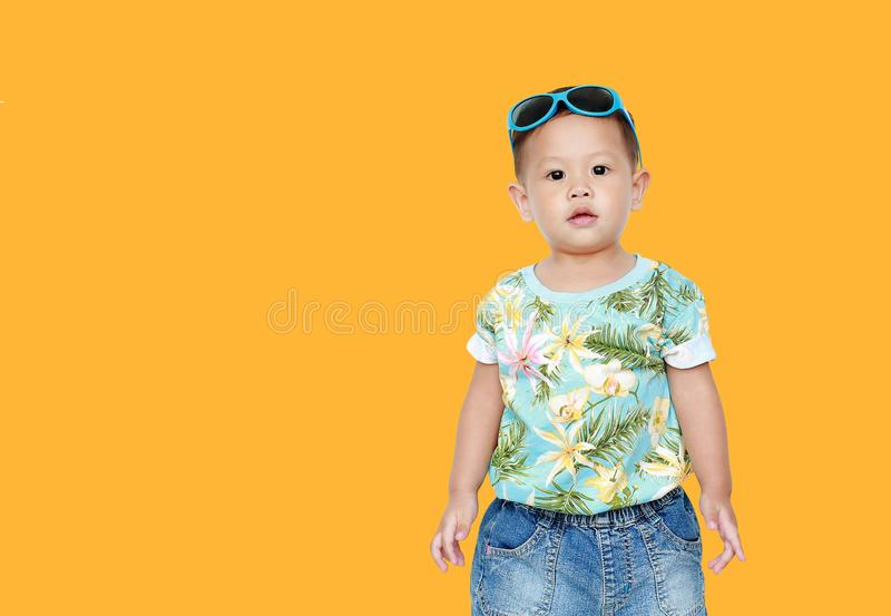 Portrait little Asian baby boy wearing a flowers summer dress and sunglasses isolated on yellow background. Summer and fashion stock photography