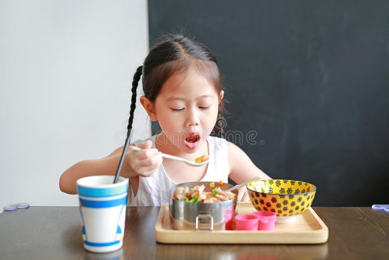 Portrait of little Asian child girl having breakfast at the morning stock photos