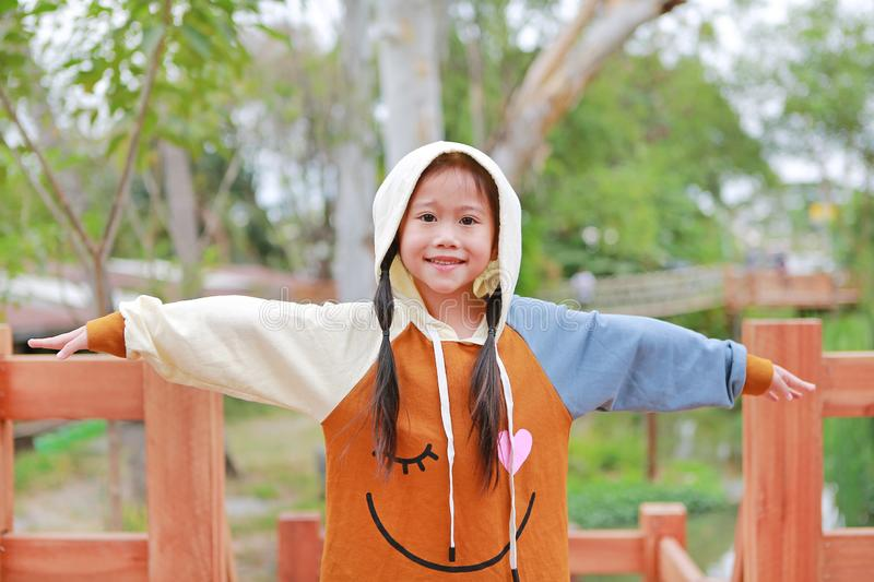Portrait of little Asian child girl in hood on head warm clothes open arms standing on balcony in the garden at winter day royalty free stock photos