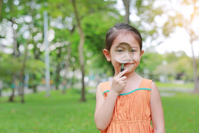 Portrait little Asian child girl looking through magnifying glass on park garden stock images