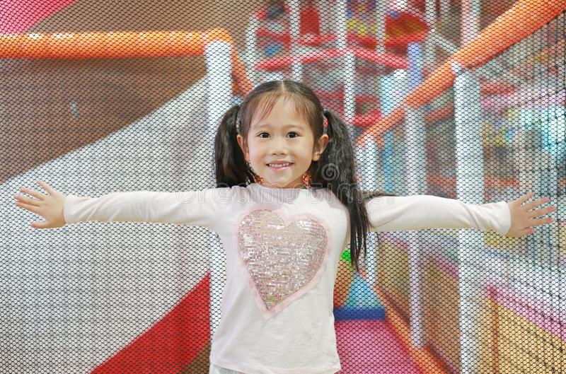 Portrait of little Asian child girl playing in indoors playground. Active girl having fun at sport center on holiday.  stock images