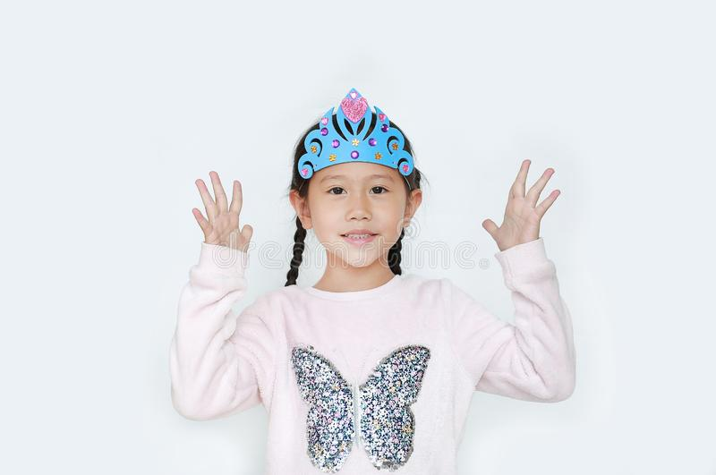 Portrait of little Asian child girl with wearing a crown toys posture open hands from eyes isolated over white background royalty free stock photos