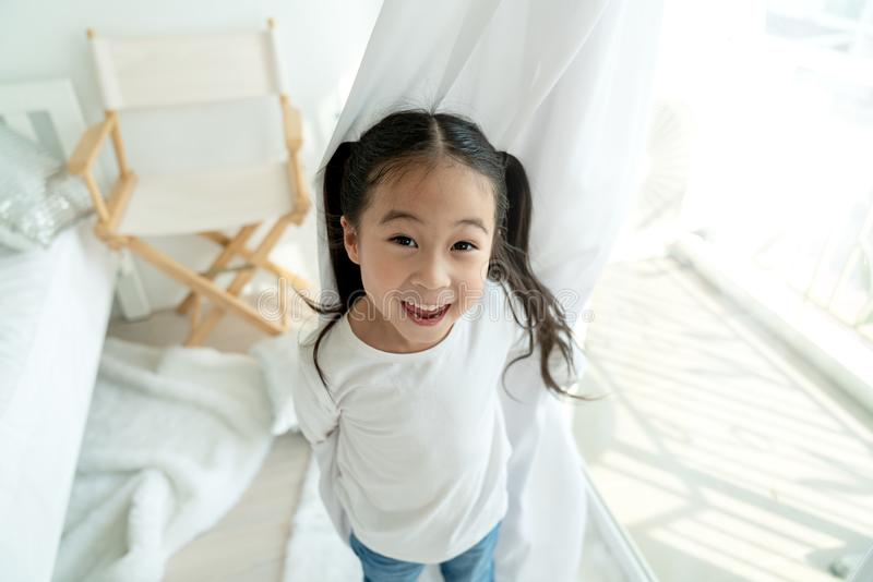 Portrait of little asian cute girl having fun in bedroom at home. Little beautiful asian sweet little girl is smile and hapiness royalty free stock photo