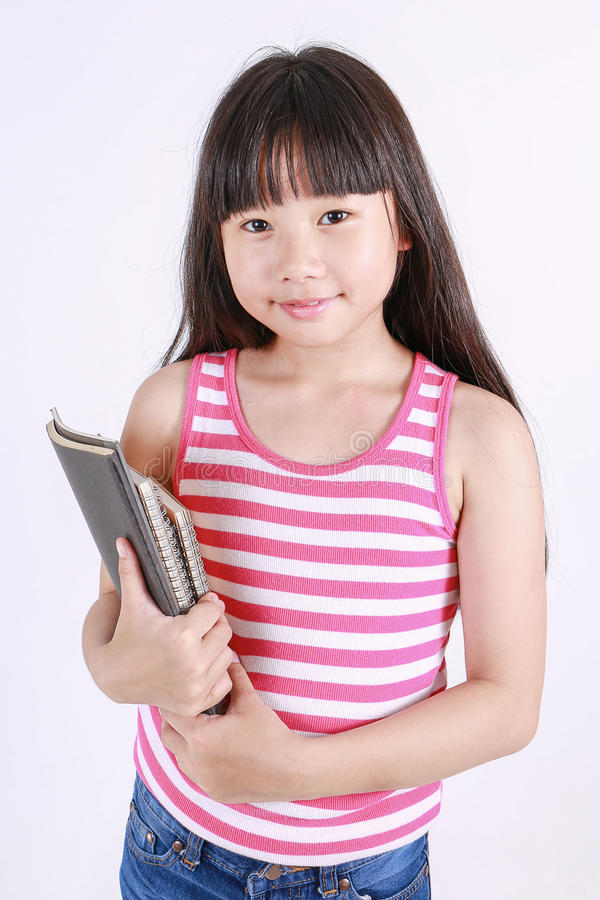 Portrait of little asian girl holding the book on isolated on white background stock photo