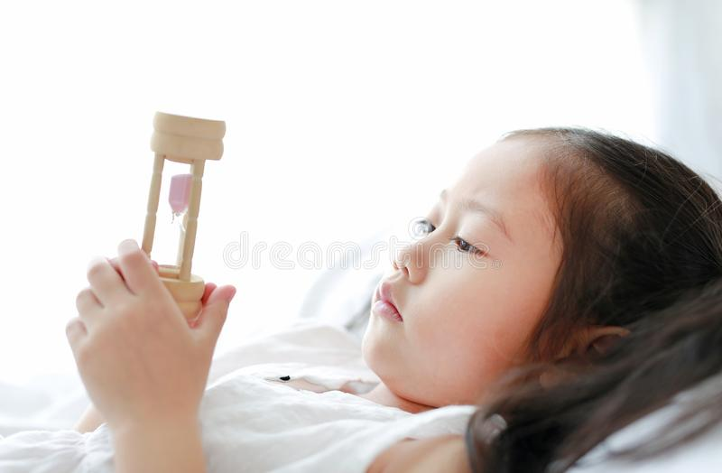 Portrait of little Asian girl looking at hourglass in hand lying on bed at home. Waiting times with sandglass. Close-up shot royalty free stock photo