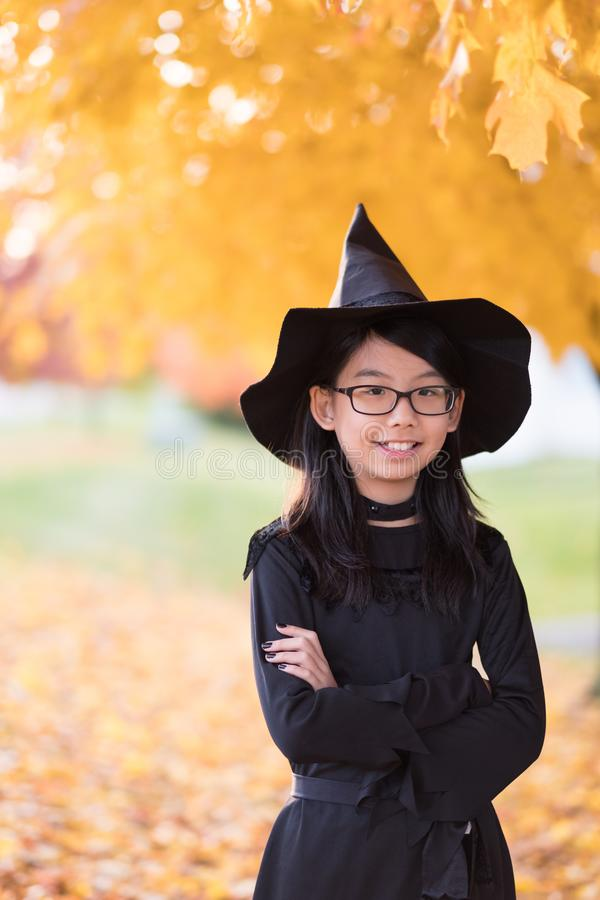 Portrait of little asian girl in witch costume royalty free stock photo