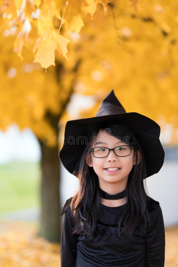 Portrait of little asian girl in witch costume royalty free stock image