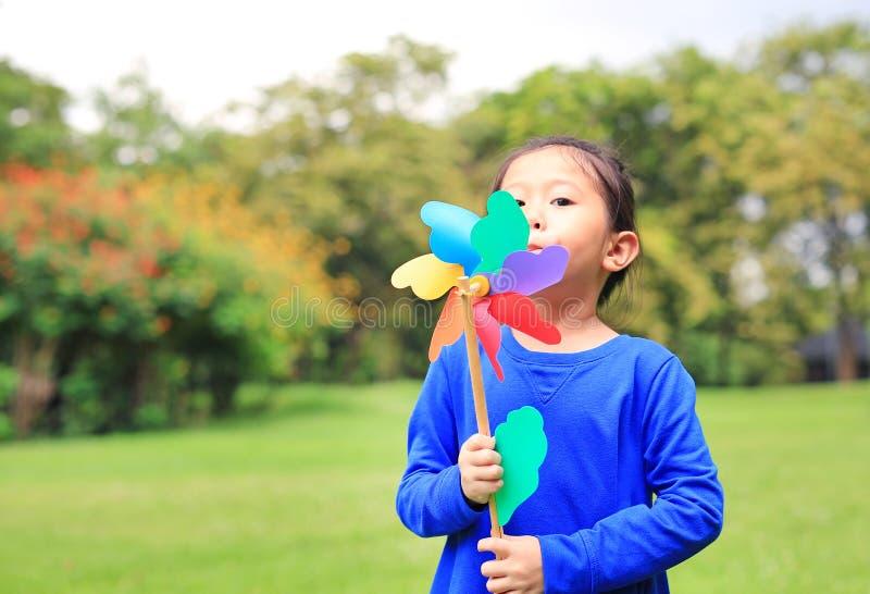 Portrait of little Asian kid girl blowing wind turbine in the summer garden royalty free stock image