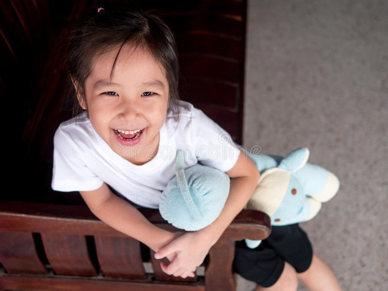 Portrait of a little asian kid girl, hug her bolster. Smile face , sit down on the wood sofa stock images