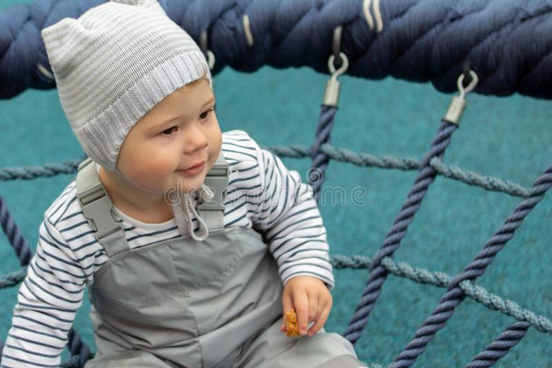 Portrait of a little baby boy girl close-up. The child walks on the playground, riding a nest swing royalty free stock photos