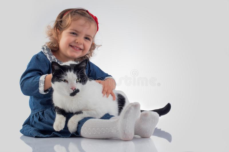 Portrait of Little baby girl holding her fluffy cat on white background.  royalty free stock image