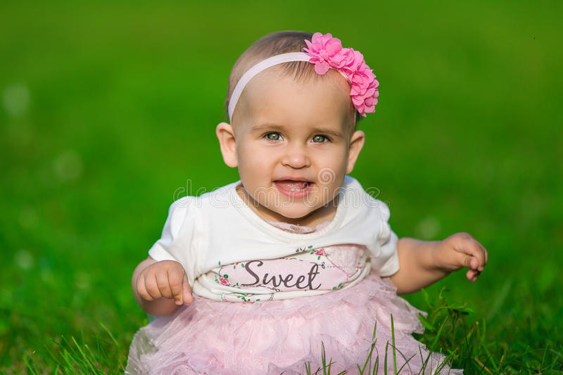 Portrait of A little baby in a pink clothes. Sits on a green grass royalty free stock photos
