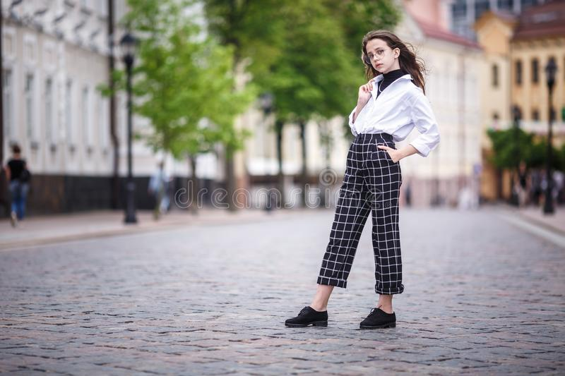 Portrait of little beautiful stylish kid girl with sunglasses and short plaid pants in city urban street.  stock photo