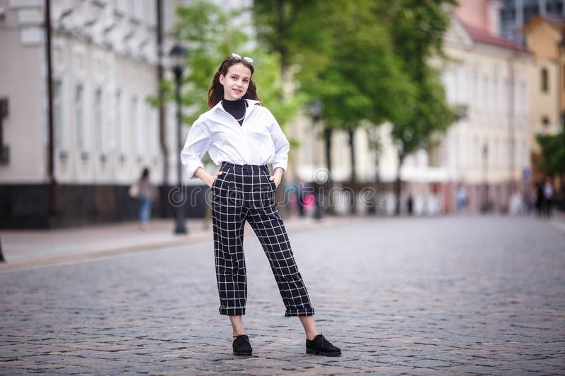 Portrait of little beautiful stylish kid girl with sunglasses and short plaid pants in city urban street.  royalty free stock photo