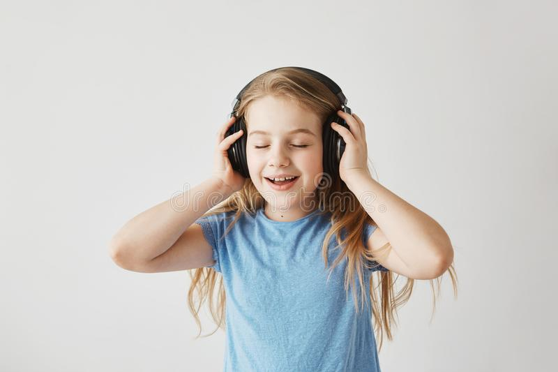 Portrait of little blonde girl in blue shirt playing with big wireless headphones, listening to music, singing song and royalty free stock images