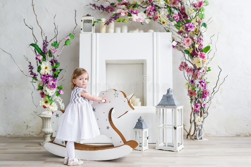 Portrait of a little blonde girl in flowers. She stand near the wooden horse rocker in the white flowers room royalty free stock image