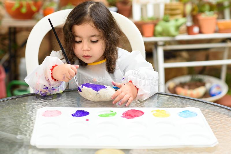 Portrait of little blonde girl painting, summer outdoor. royalty free stock image