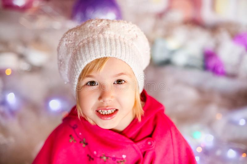 Portrait of little blonde smiling girl with white beret, red boots, pink cloak. Christmas and New Year theme royalty free stock photo