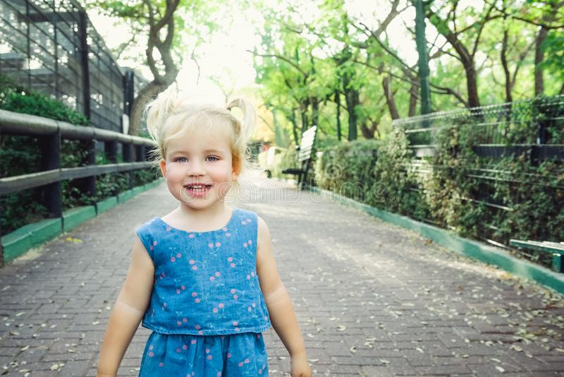 Portrait of little blondy toddler Girl Smiling at Camera. Happy kid walking outdoors in the park or zoo. Family recreation, leasur stock photography