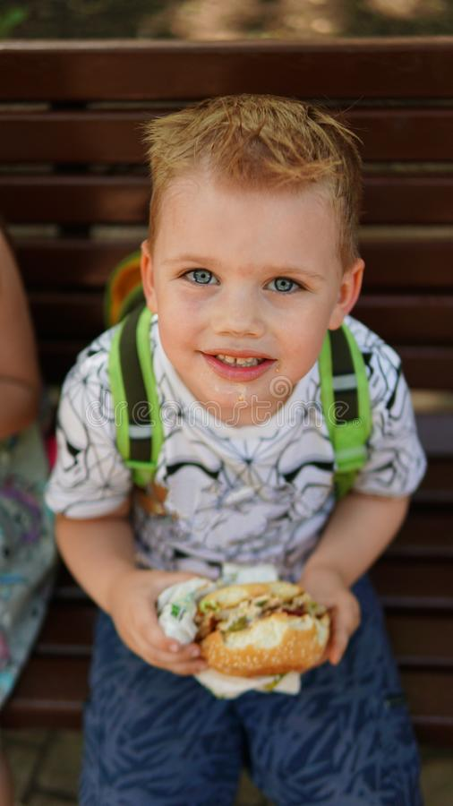 Portrait of a little boy . A child eating hamburger in the Park stock photography