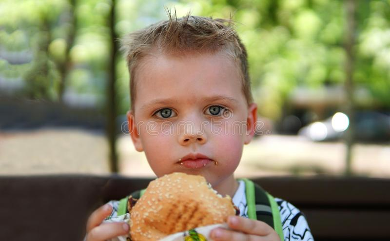 Portrait of a little boy . A child eating hamburger in the Park stock photos