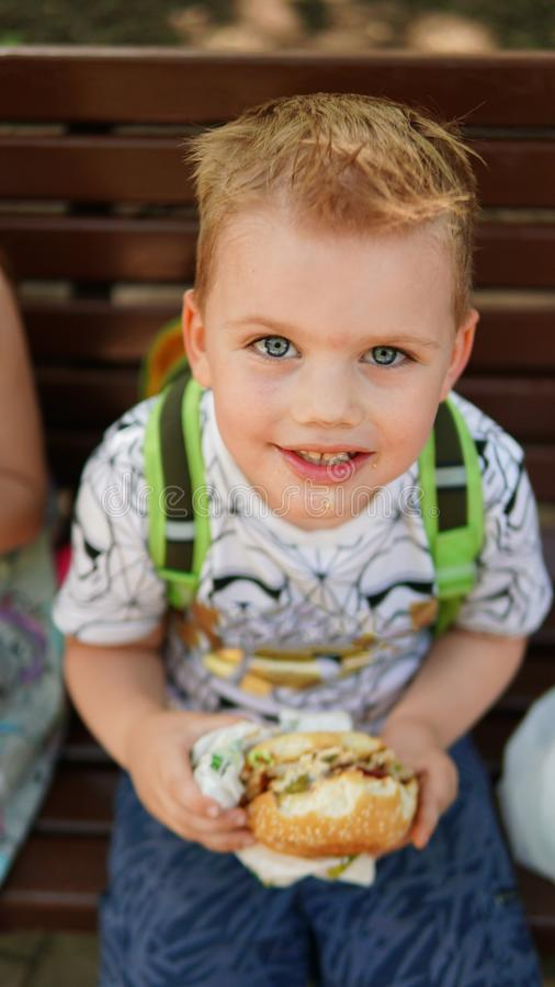 Portrait of a little boy . A child eating hamburger in the Park royalty free stock images