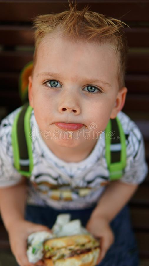 Portrait of a little boy . A child eating hamburger in the Park royalty free stock photography