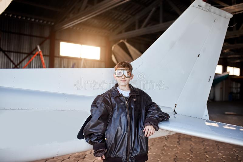 Portrait of little boy standing besides light white airplane tail inside aircraft shed. Portrait of little boy dressed in large black leather pilot jacket and stock photos