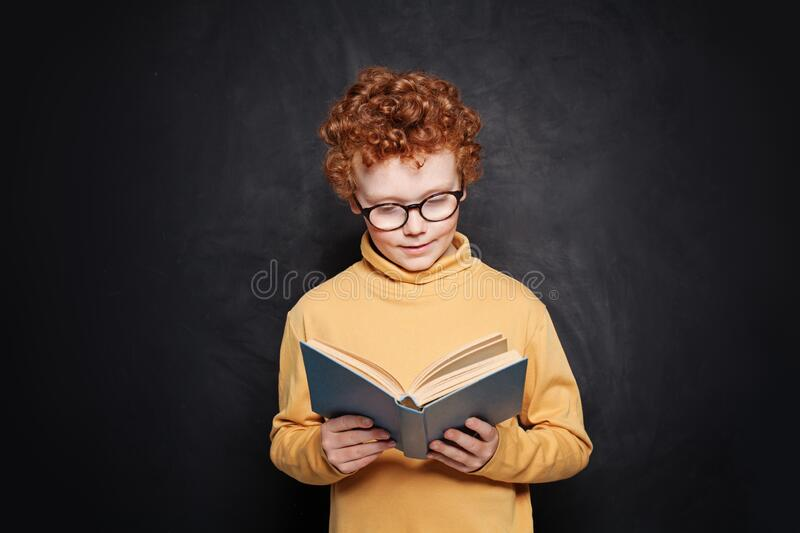 Portrait of little boy in glasses reading a book against blackboard royalty free stock images