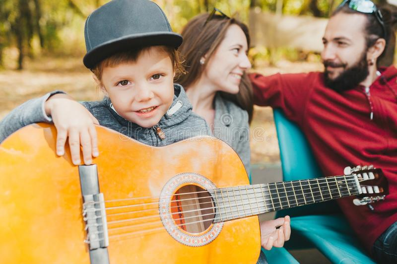 Portrait of little boy in hat playing guitar outdoors. His parents at a background stock photos