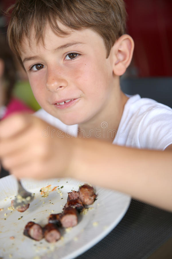 Portrait of little boy having lunch. Portrait of young kid eating grilled food in summer royalty free stock photos