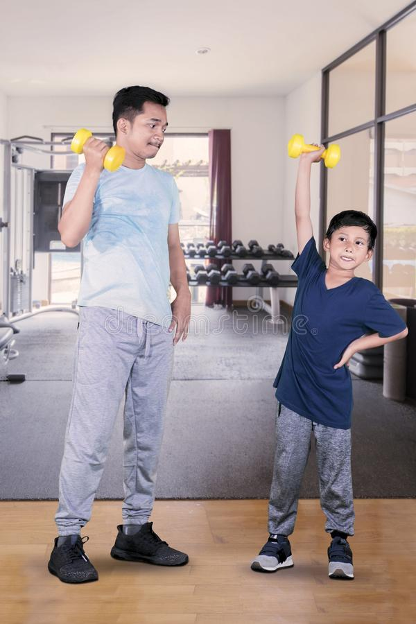 Child and father lifting a dumbbell royalty free stock photography
