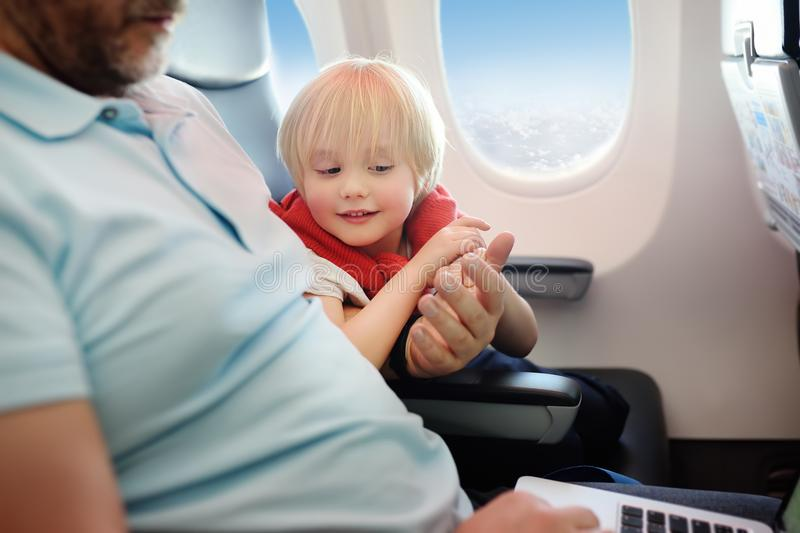 Portrait of little boy with his father during traveling by an airplane royalty free stock images