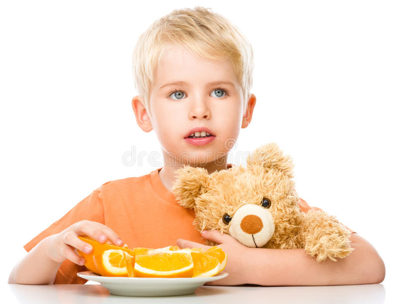 Portrait of a little boy with his teddy bear. And oranges, isolated over white royalty free stock photos