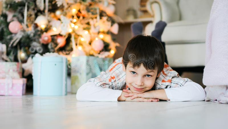A portrait of a little boy lying on the floor near fir tree stock images